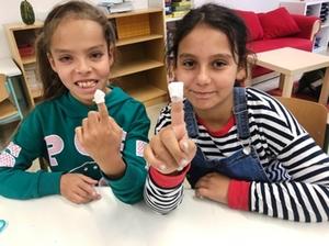 Zwei Mädchen haben sich gegenseitig einen Fingerkuppenverband beim Erste Hilfe Kurs angelegt