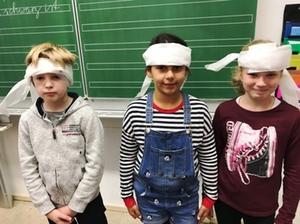 Drei Schüler mit einem Kopfverband beim Erste Hilfe Kurs