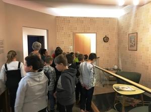 Die Lehrerin erklärt den Schülern die Ausstellung des Stadtmuseums, Schüler schauen sich gespannt Ausstellungsstücke an
