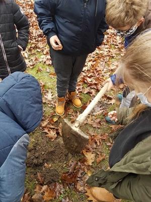 Kinder graben mit einer Schaufel ein Loch für die Blumenzwiebeln