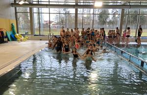 Kinder auf dem Weg ins Wasser in der Schulschwimmhalle